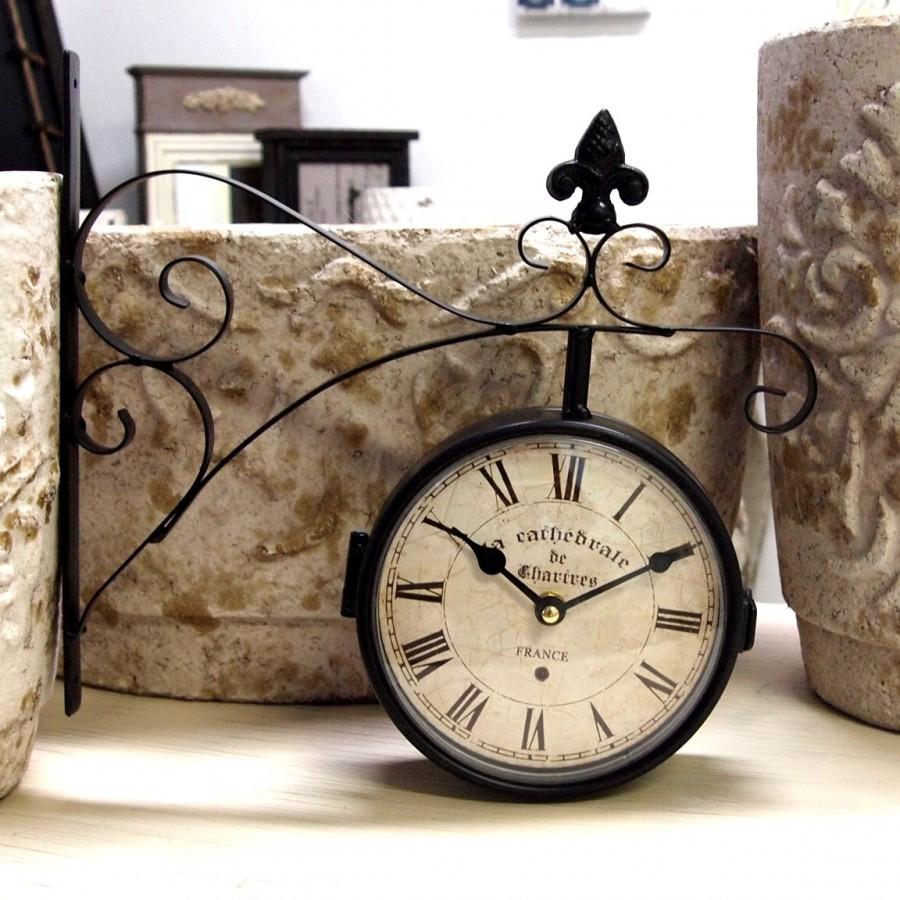 Zegar Dworcowy o metalowej konstrukcji ozdobiony lilijką i rzymskimi cyframi.