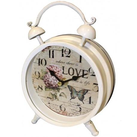 Zegar przypominający biały budzik z tarczą w stylu prowansalskim