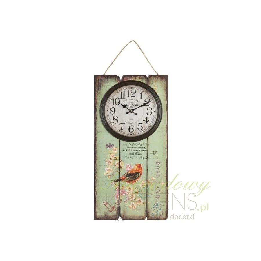 Wiszący zegar umieszczony na zielonych deskach.