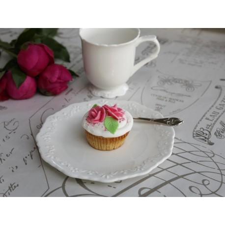 Okrągły biały talerz deserowy, a na nim babeczka