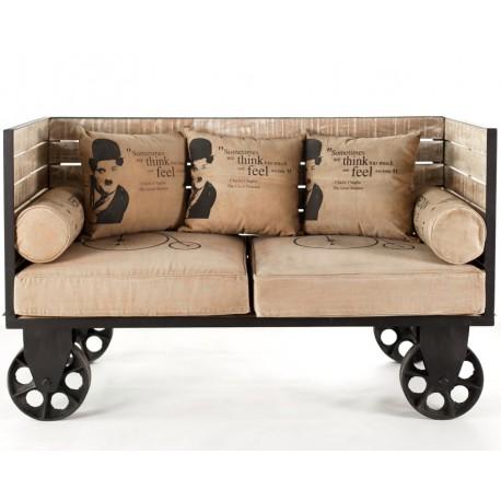 Dwuosobowa sofa industrialna Mazine na metalowych kółkach z beżową tapicerką to okaz pięknego mebla służącego wypoczynkowi.