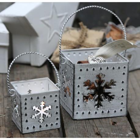 Białe latarnie z azurowymi ściankami, które zostały wycięte na kształt śnieżynek. Lampion z śnieżynką ma biały kolor oraz praktyczny uchwyt.