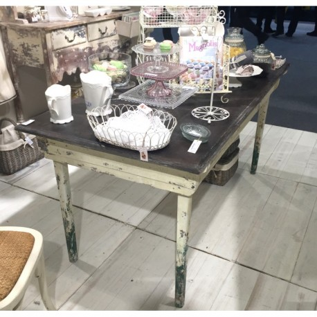Mocno przecierany stół z jasną podstawą i ciemnym blatem