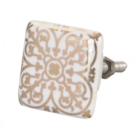 Kwadratowa biała gałka wykonana z ceramiki ozdobiona złotym wzorem.