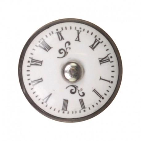 biała, okrągła gałka ozdobna posiadająca czarne, rzymskie numery