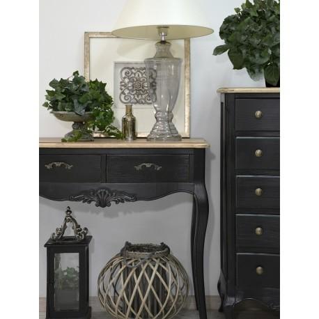 Elegancka konsola w kolorze czarnym ma dwie szufladki oraz brązowy blat. Jej ozodobą jest atrakcyjny ornament pod blatem.