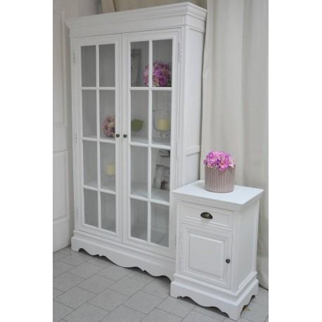 Przeszklona, duża witryna w stylu francuskim na biały kolor i przestronne wnętrze, którego zawartość ujawniają szklane drzwi.