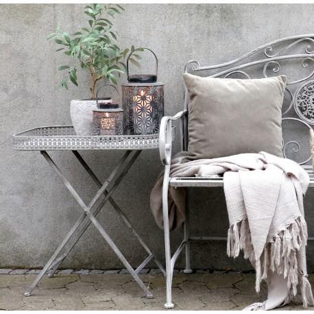 Szary stolik metalowy z blatem w formie dekoracyjnej tacy to doskonałe miejsce na dekoracje takie jak lampion czy świece.